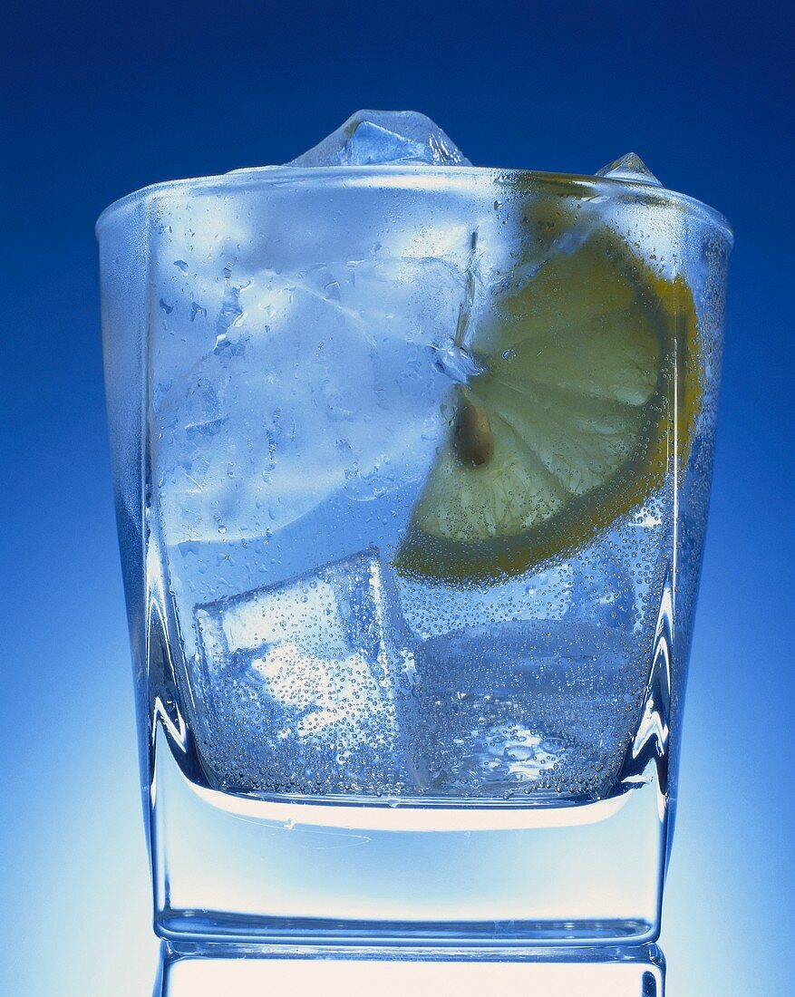 Glass of gin & tonic with ice & lemon against blue background