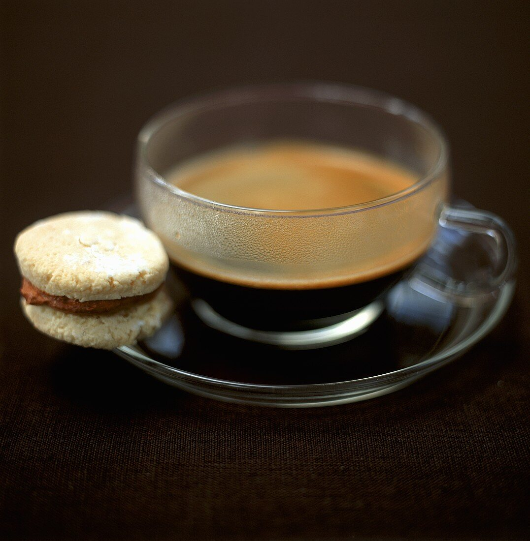 Espresso in glass cup and a biscuit with chocolate cream