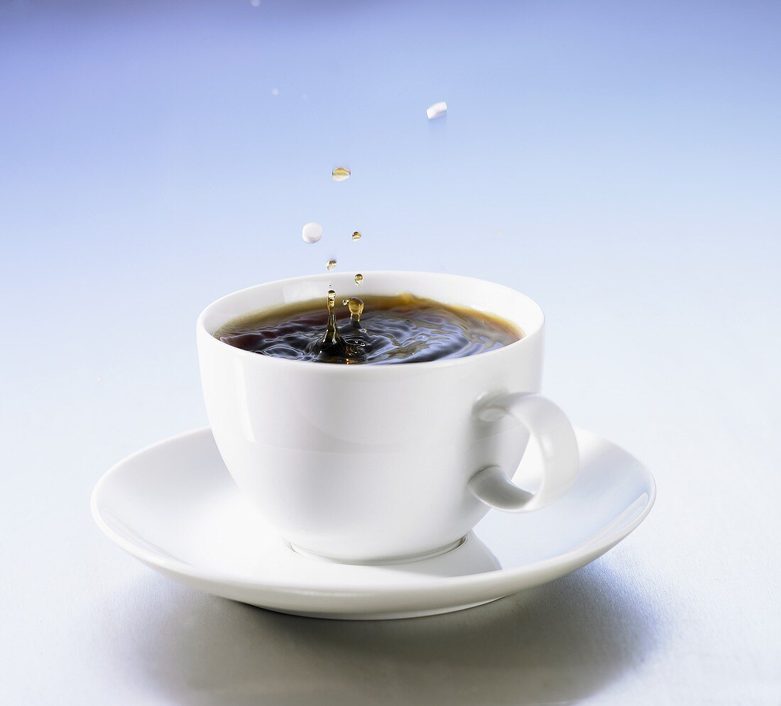 Coffee cup with sweetener falling into it