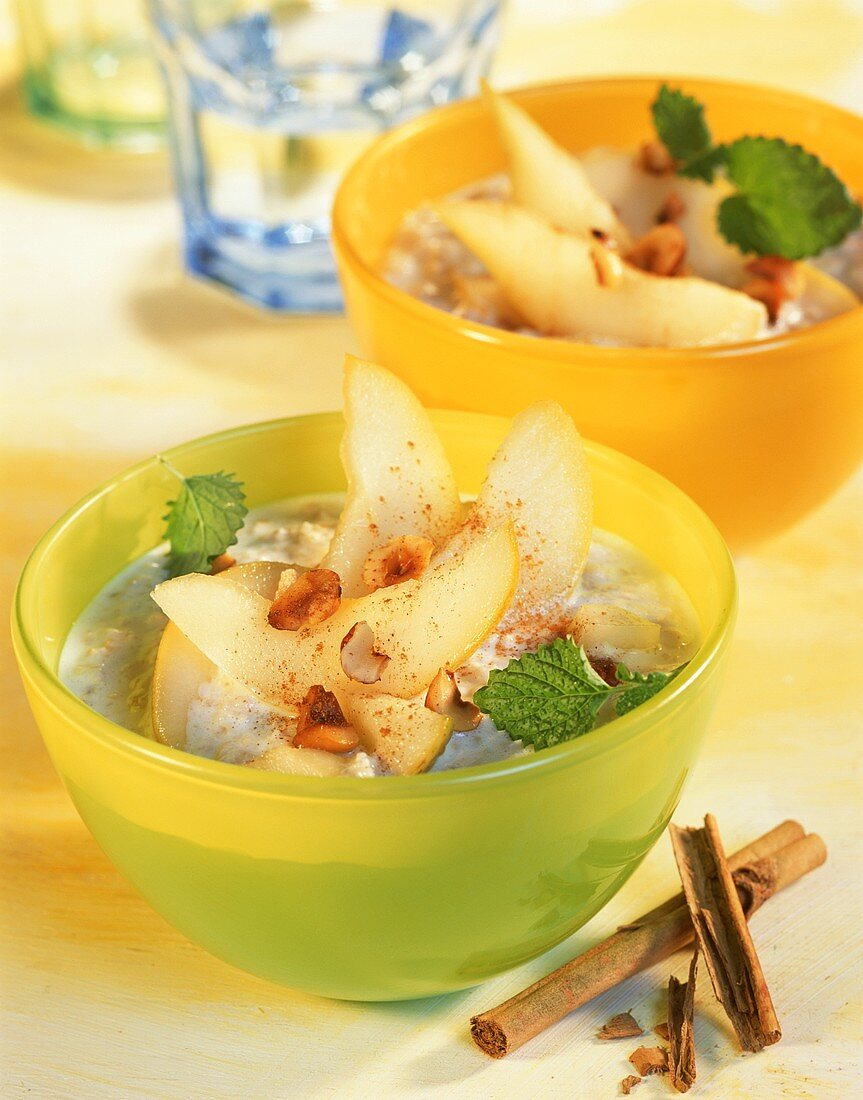 Two bowls of porridge with pears and hazelnuts