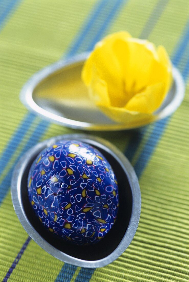 Blue Easter egg and yellow tulip in egg-shaped bowls