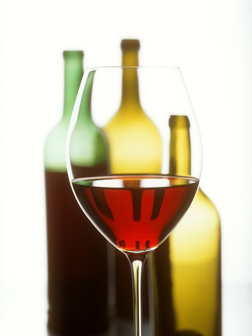 Glass of red wine in front of three wine bottles