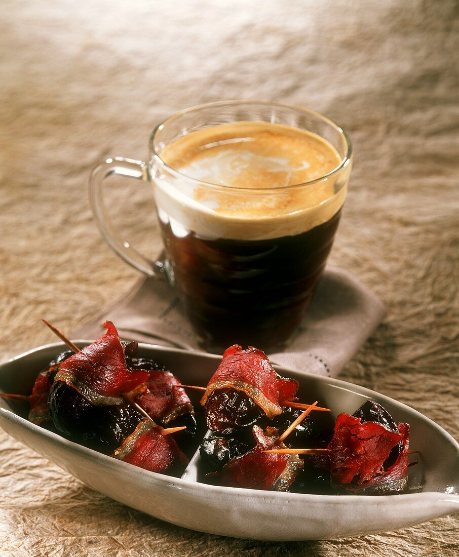 Plums wrapped in bacon and a glass of Irish Coffee