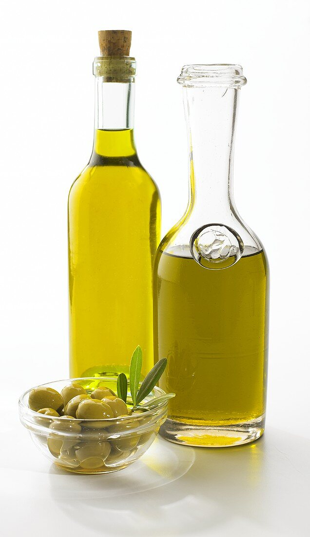 A bowl of green olives and two bottles of olive oil