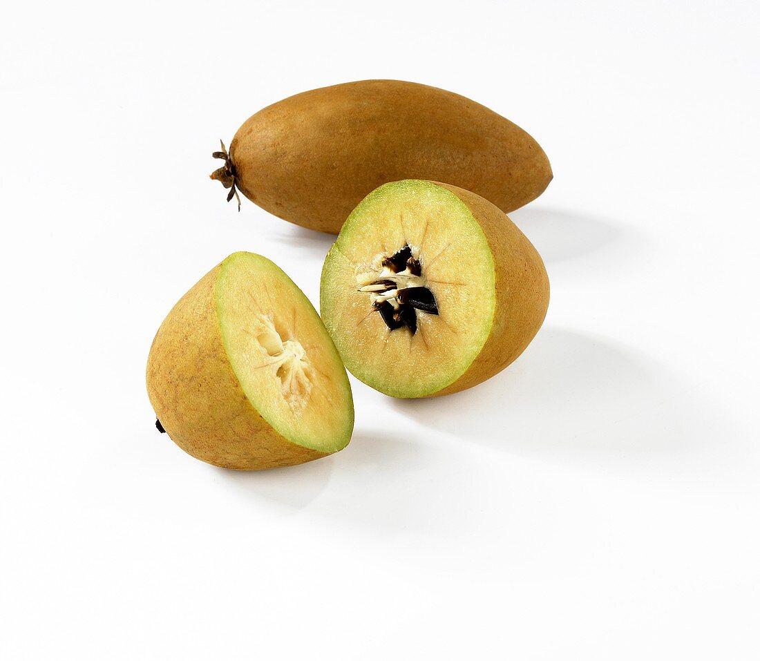 Whole and halve sapodilla (the fruit of the sapodilla tree)