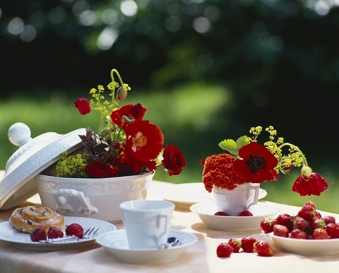Table decoration with poppies, roses and celosias