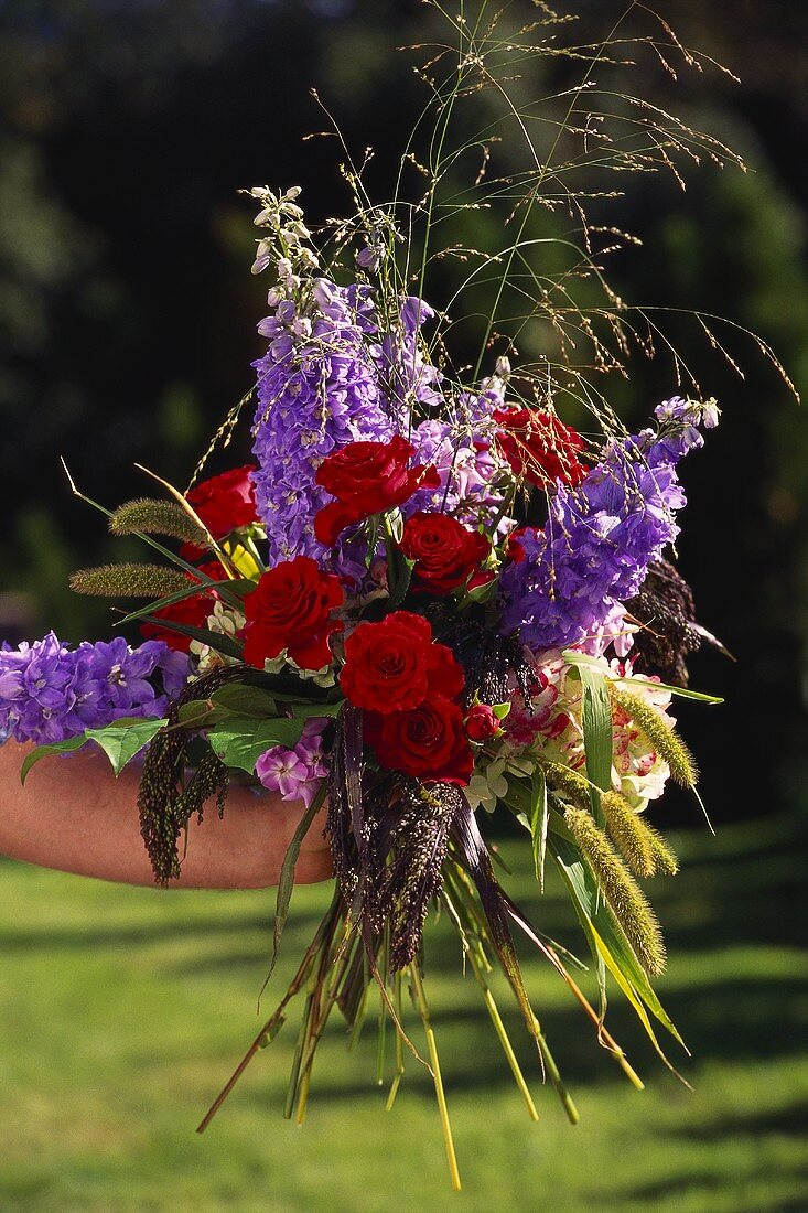 Bouquet of red roses and larkspur