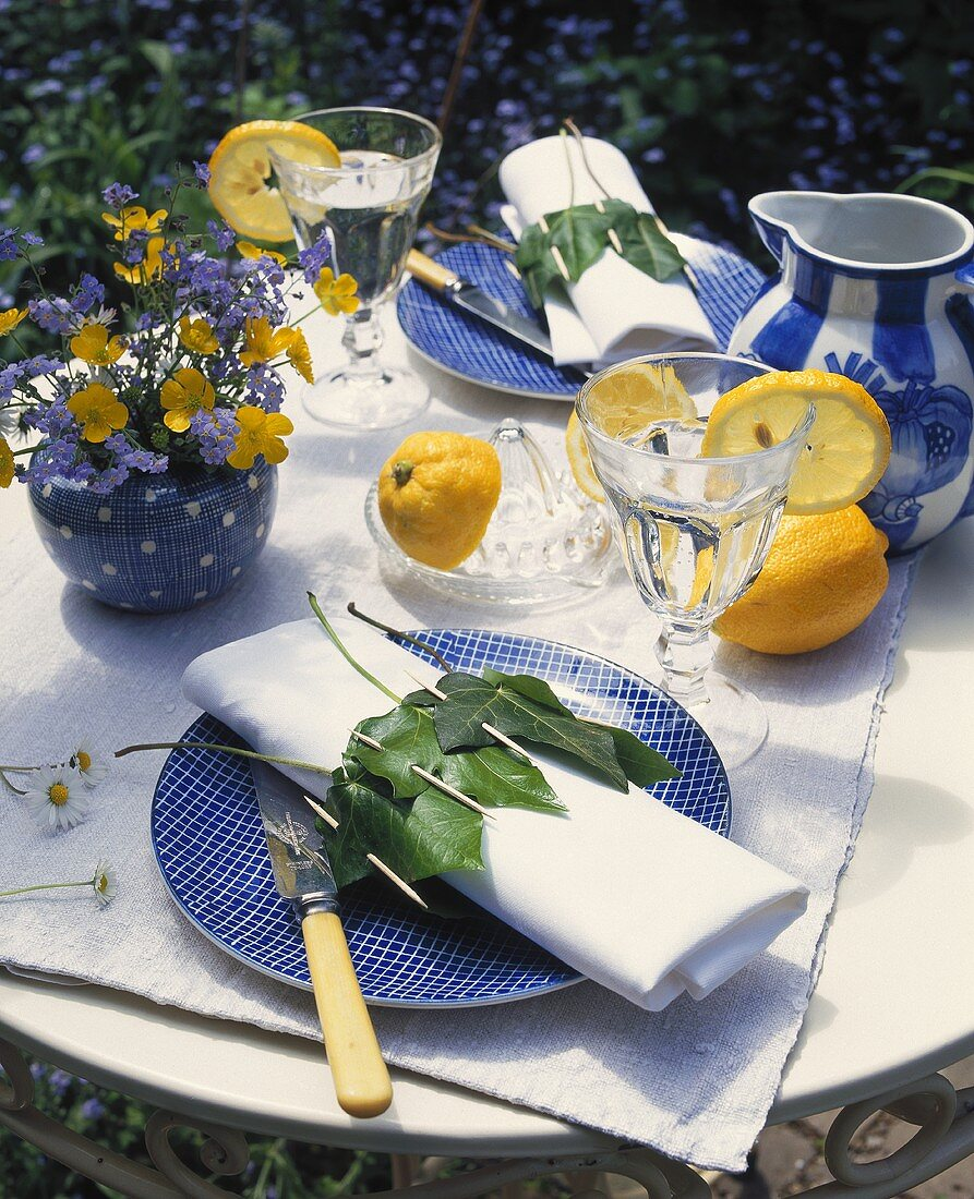 Laid table with forget-me-nots and buttercups in vase