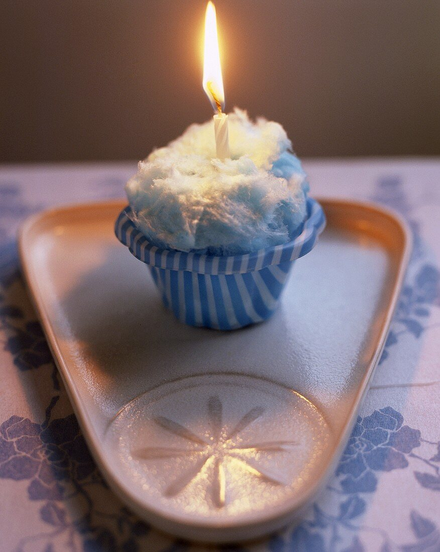 Cup-cake with candyfloss and burning candle for birthday