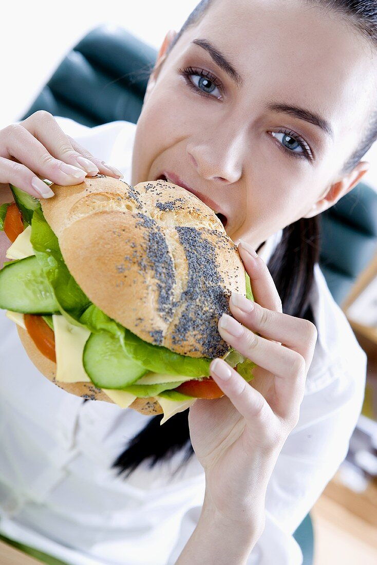Businesswoman biting into a filled poppy seed roll