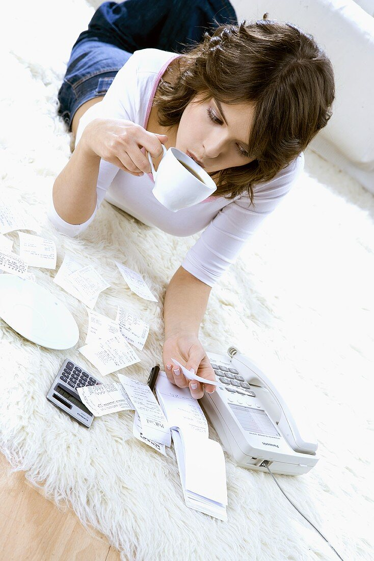 Young woman lying on floor, drinking tea & doing paperwork