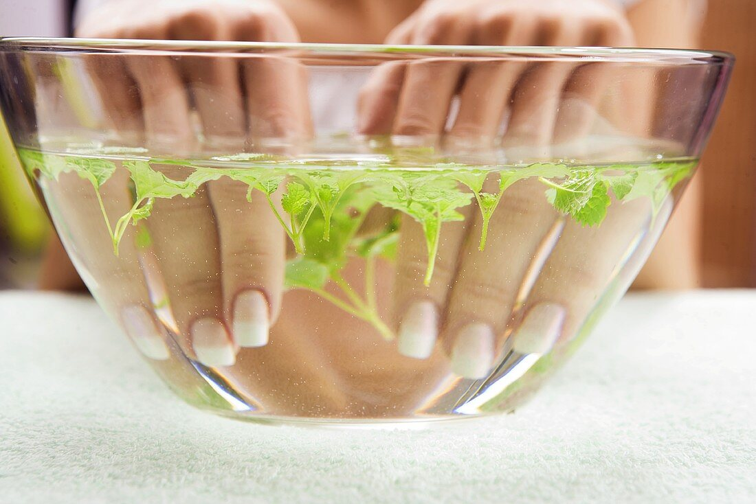 Young woman bathing her hands in herb water
