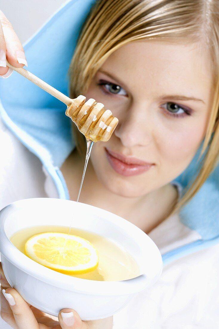 Young woman letting honey run into lemon tea