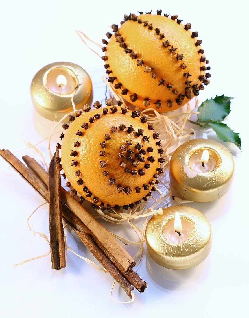 Oranges studded with cloves, cinnamon sticks and candles