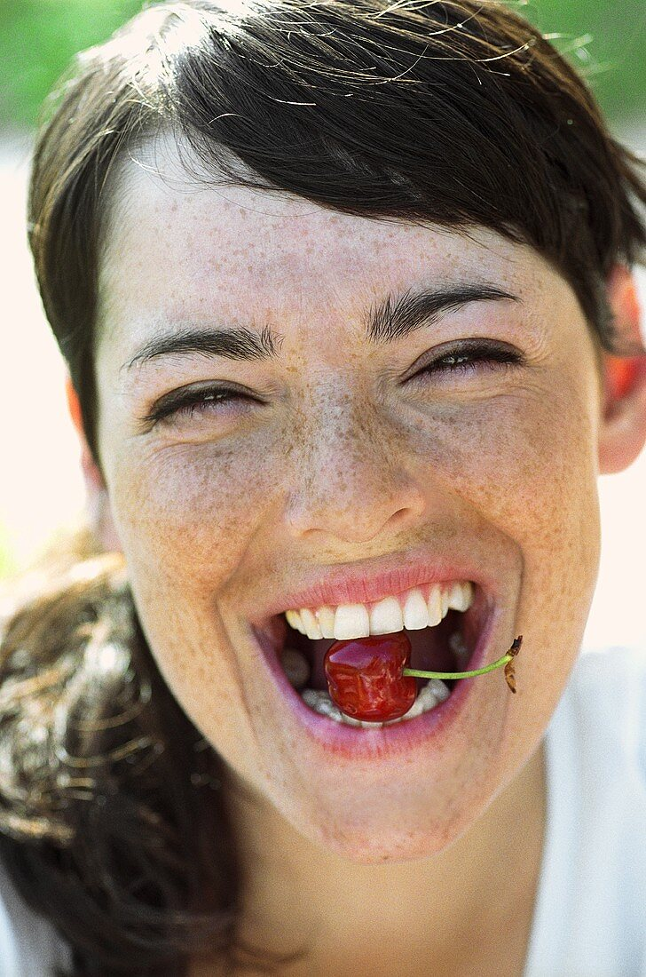Portrait of a young woman with a cherry in her mouth