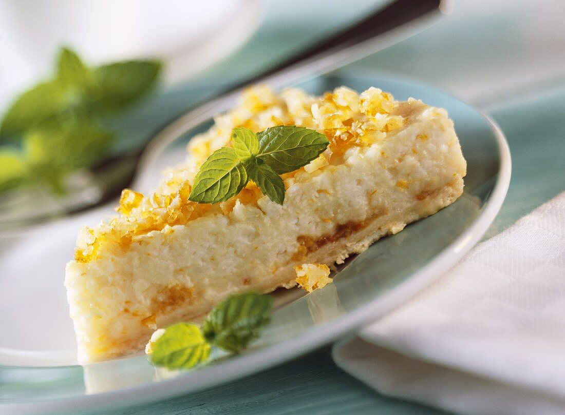 Piece of orange rice tart with mint leaves