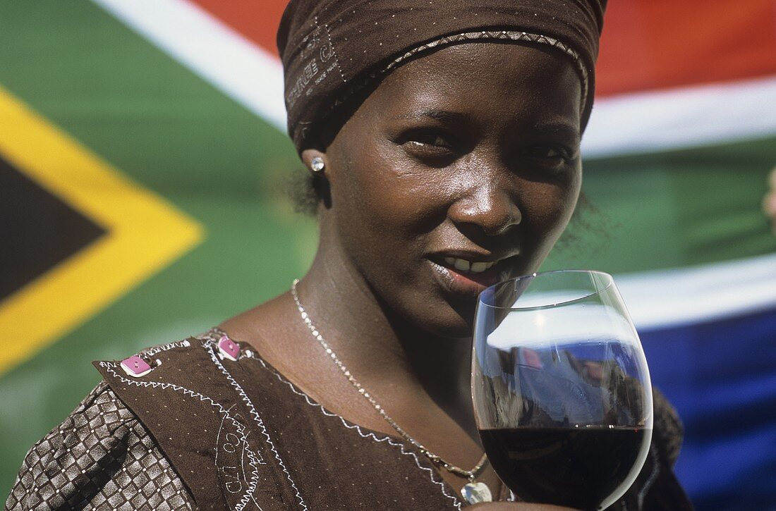 Woman drinking a glass of red wine in front of S. African flag