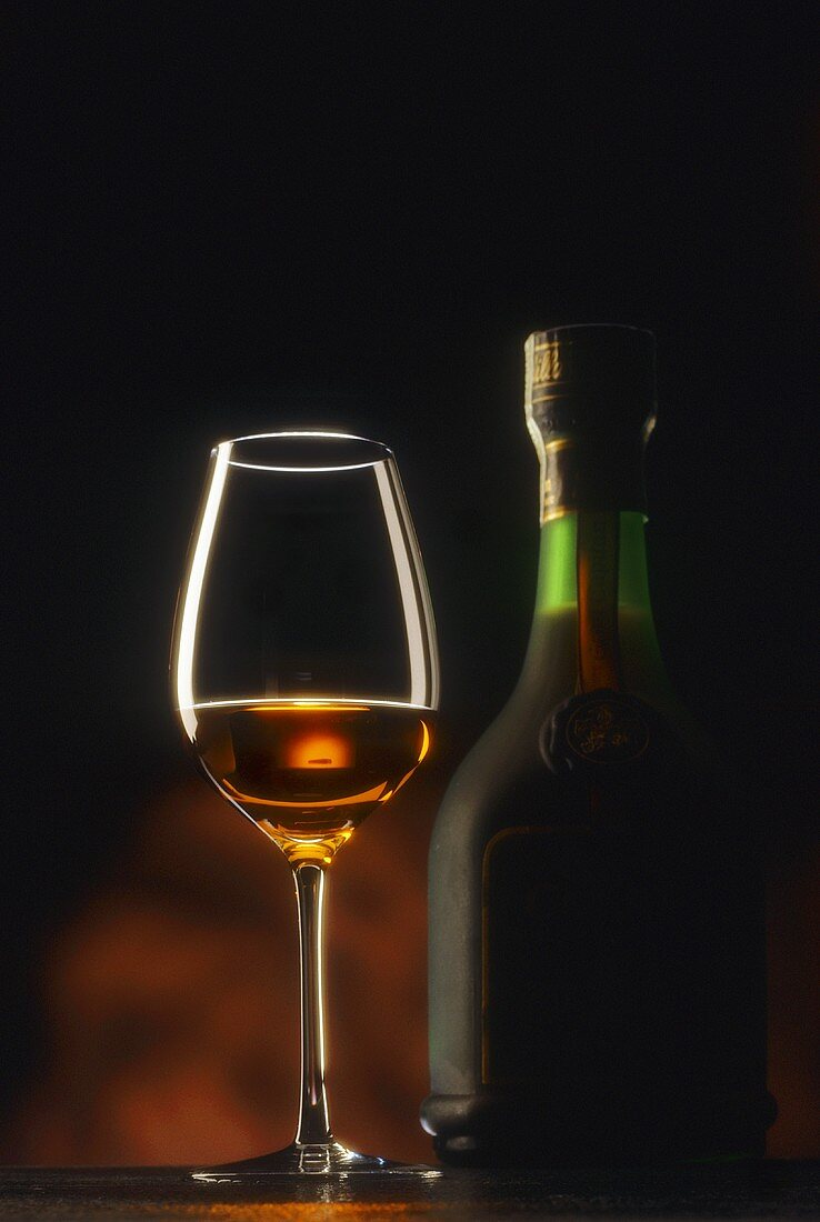 A glass and a bottle of cognac