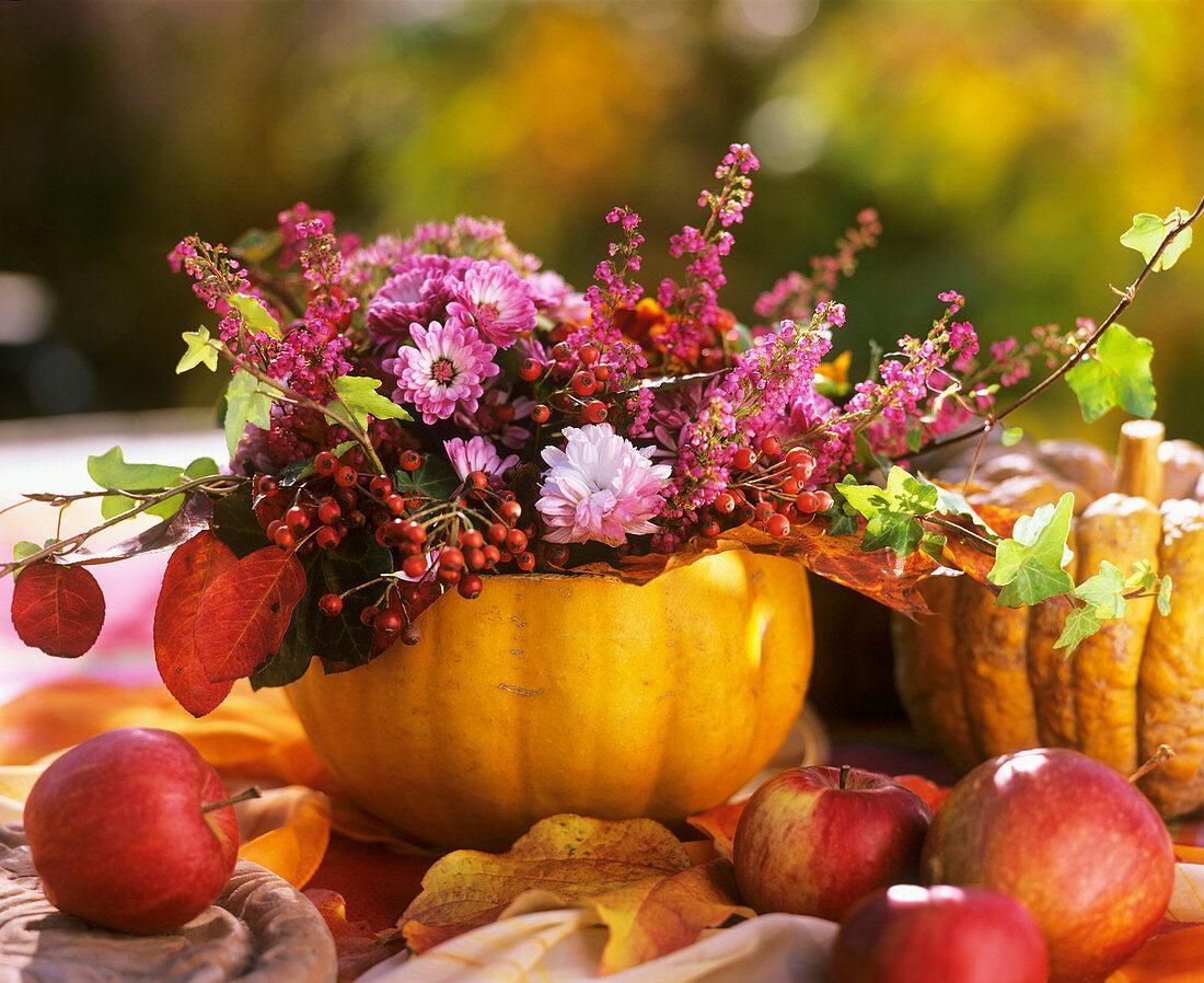 Chrysanthemums, rose hips, heather & serviceberries in pumpkin