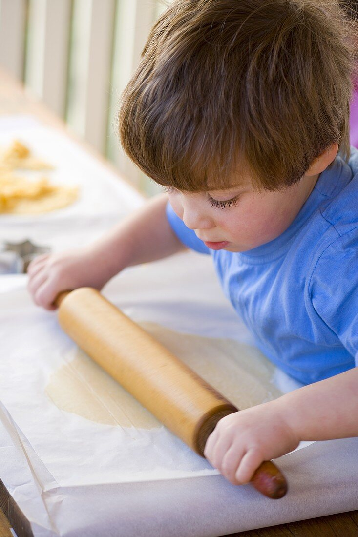 Small boy rolling out biscuit dough between greaseproof paper