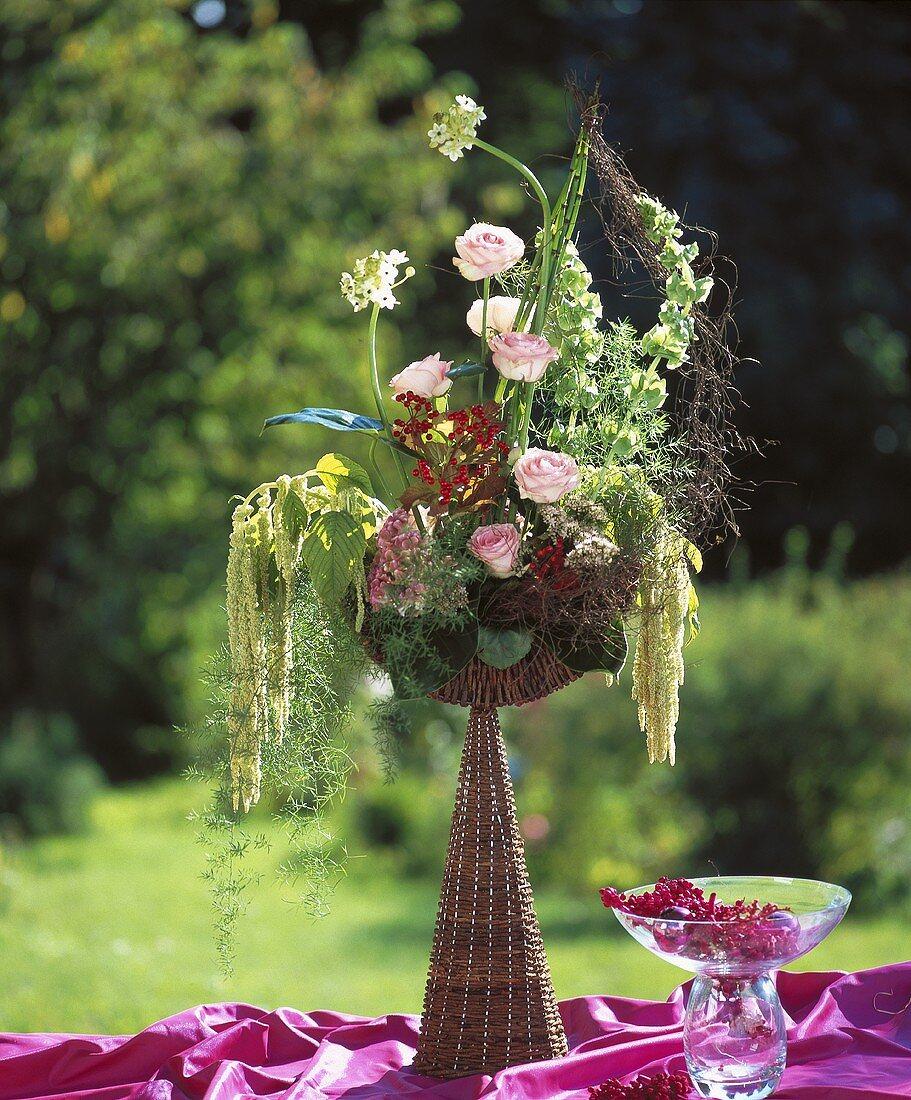 Wicker goblet with roses, celosia, sedum, ornamental asparagus
