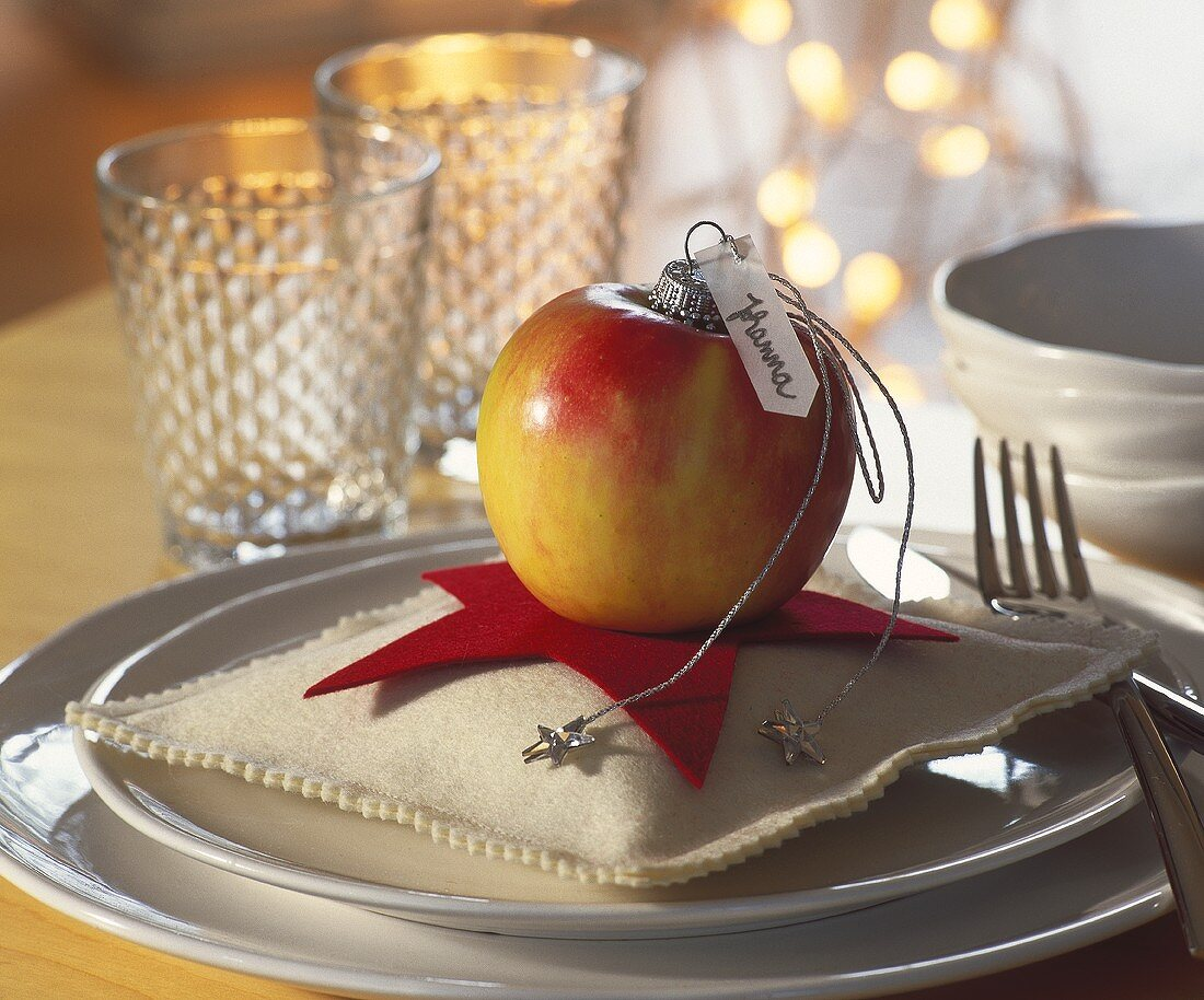 Apple with place card on small star-shaped cushion