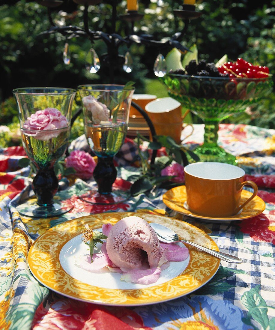 Summery table laid for coffee with roses, fruit and ice cream