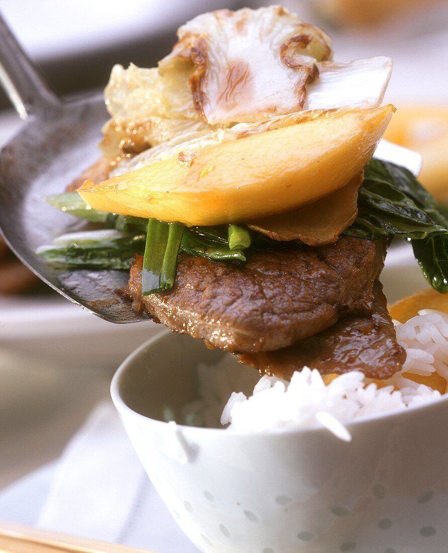 Fried beef slice with vegetables, mango; bowl of rice