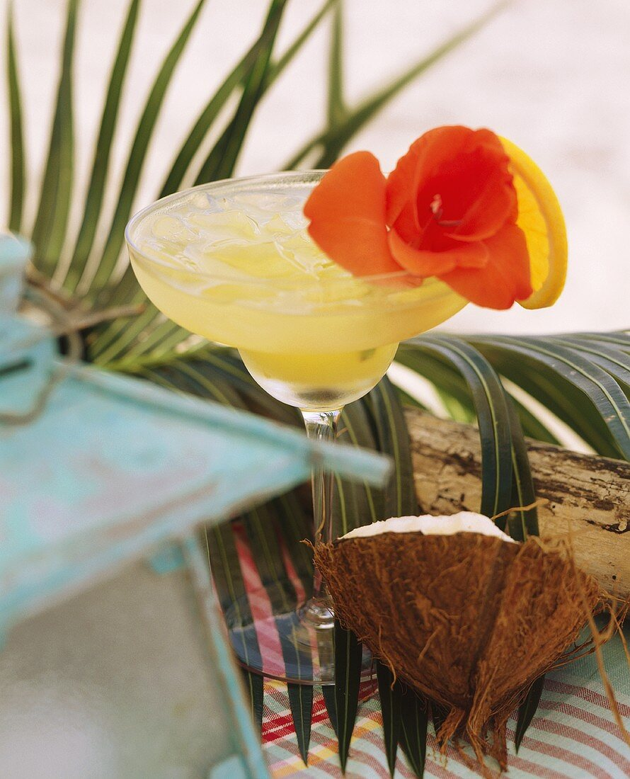 Caribbean drink with ice cubes, slice of orange, flower