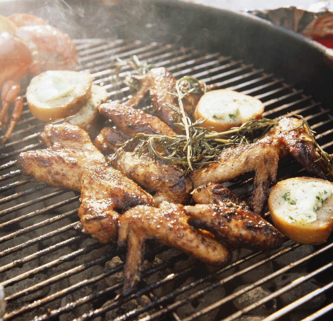 Barbecuing marinated chicken wings with herbs