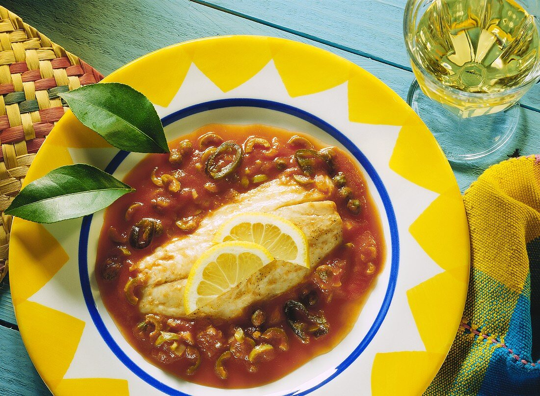 Red snapper with tomatoes, olives, peppers and lemons
