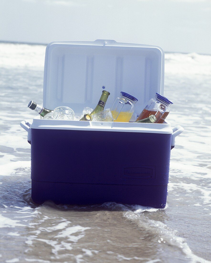 Coolbox with drinks bottles, juice cans, & glasses in sea