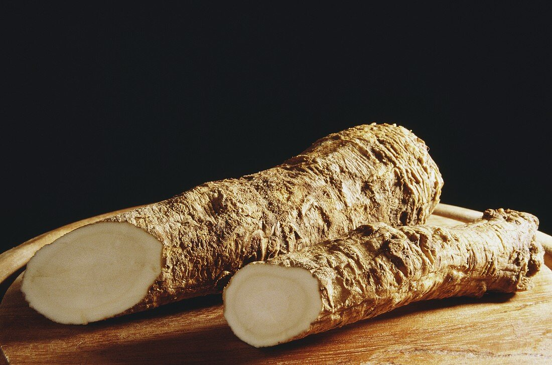 Two horseradish roots on wooden plate