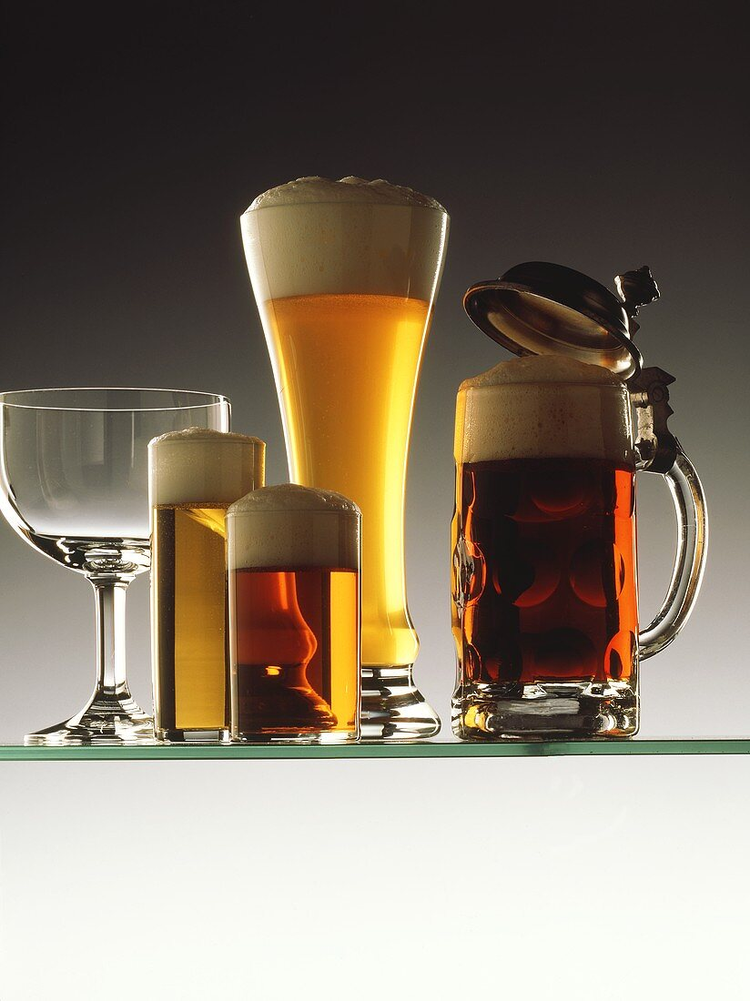 Various full beer glasses and one empty glass