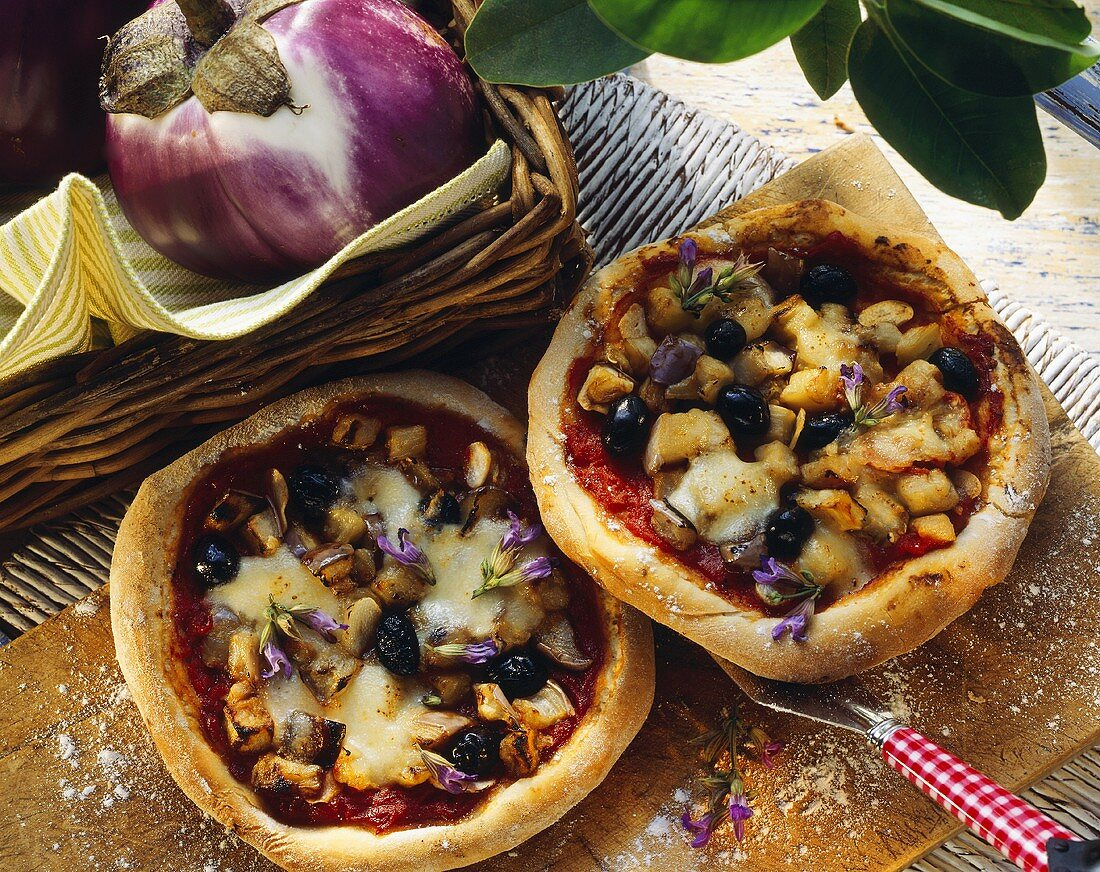 Aubergine pizza with black olives and sage flowers
