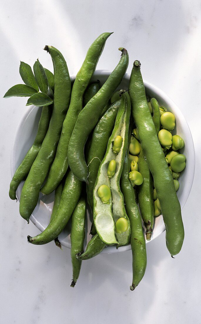 Green bean pods, one opened, and beans in bowl