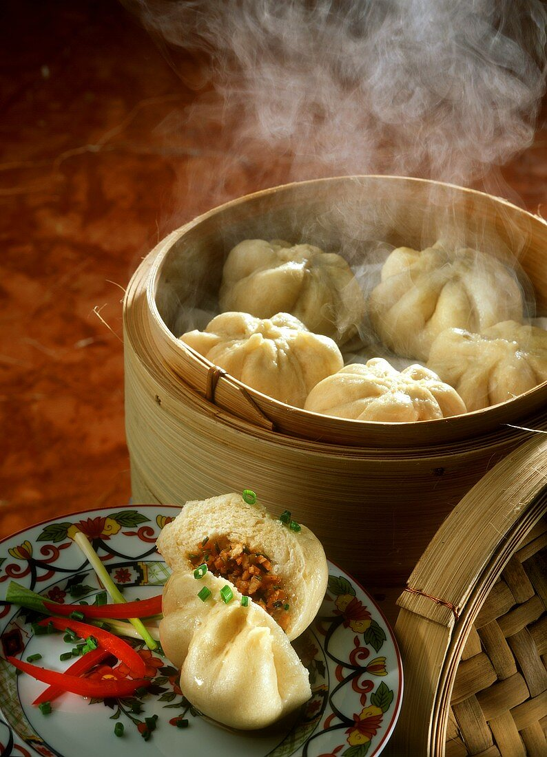 Chinese filled yeast rolls on plate and bamboo steamer