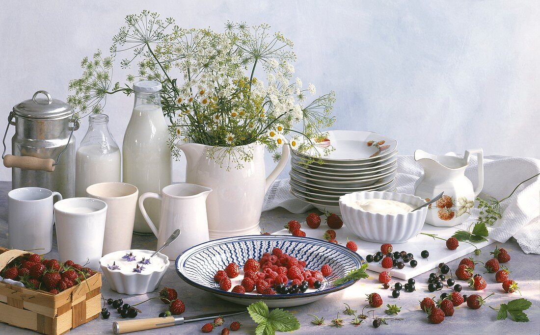 Still life with berries, milk, cream and meadow flowers
