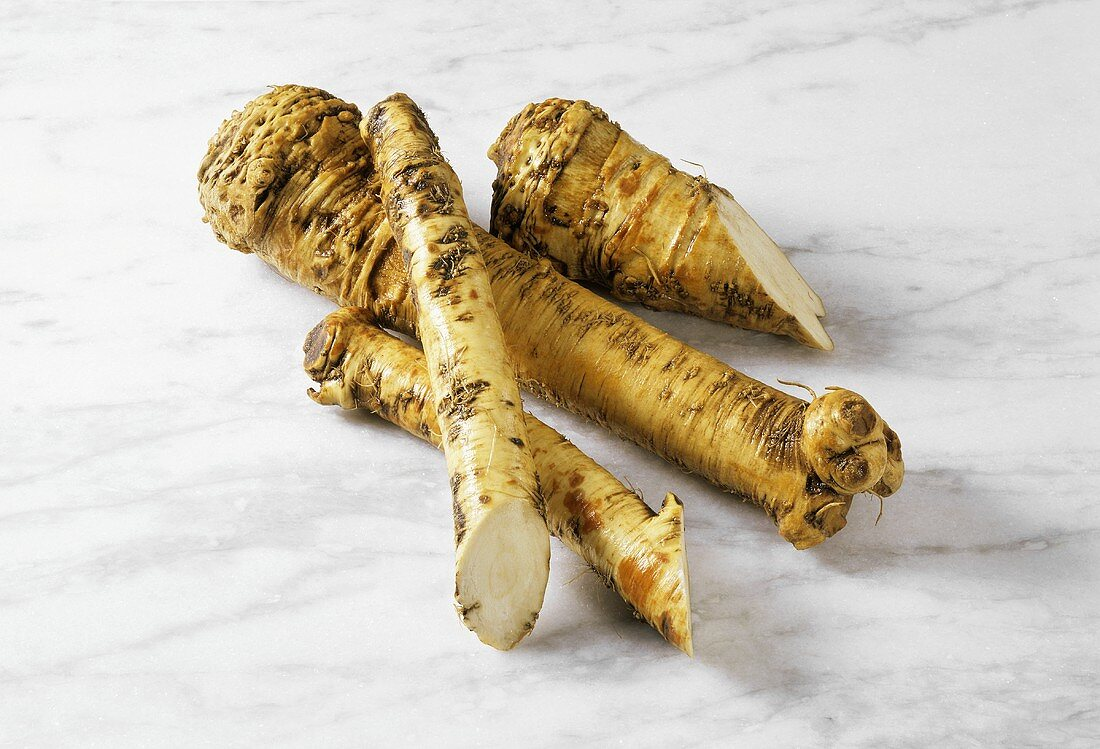 Horseradish root, whole and cut open, on marble surface