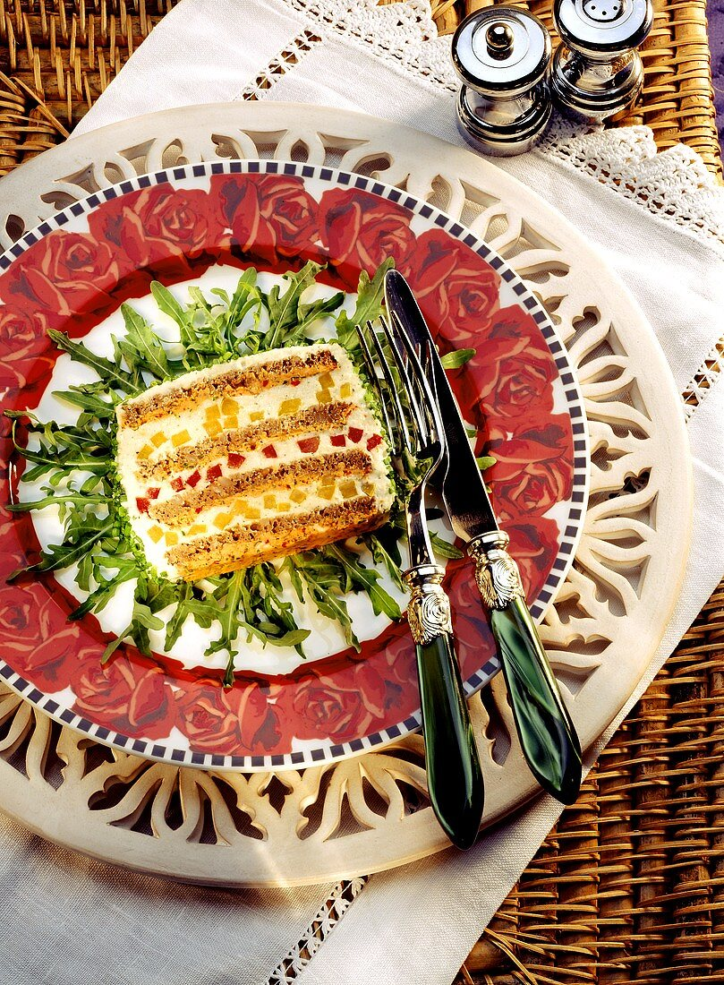 Layered cheese pate with pepper on plate with rocket
