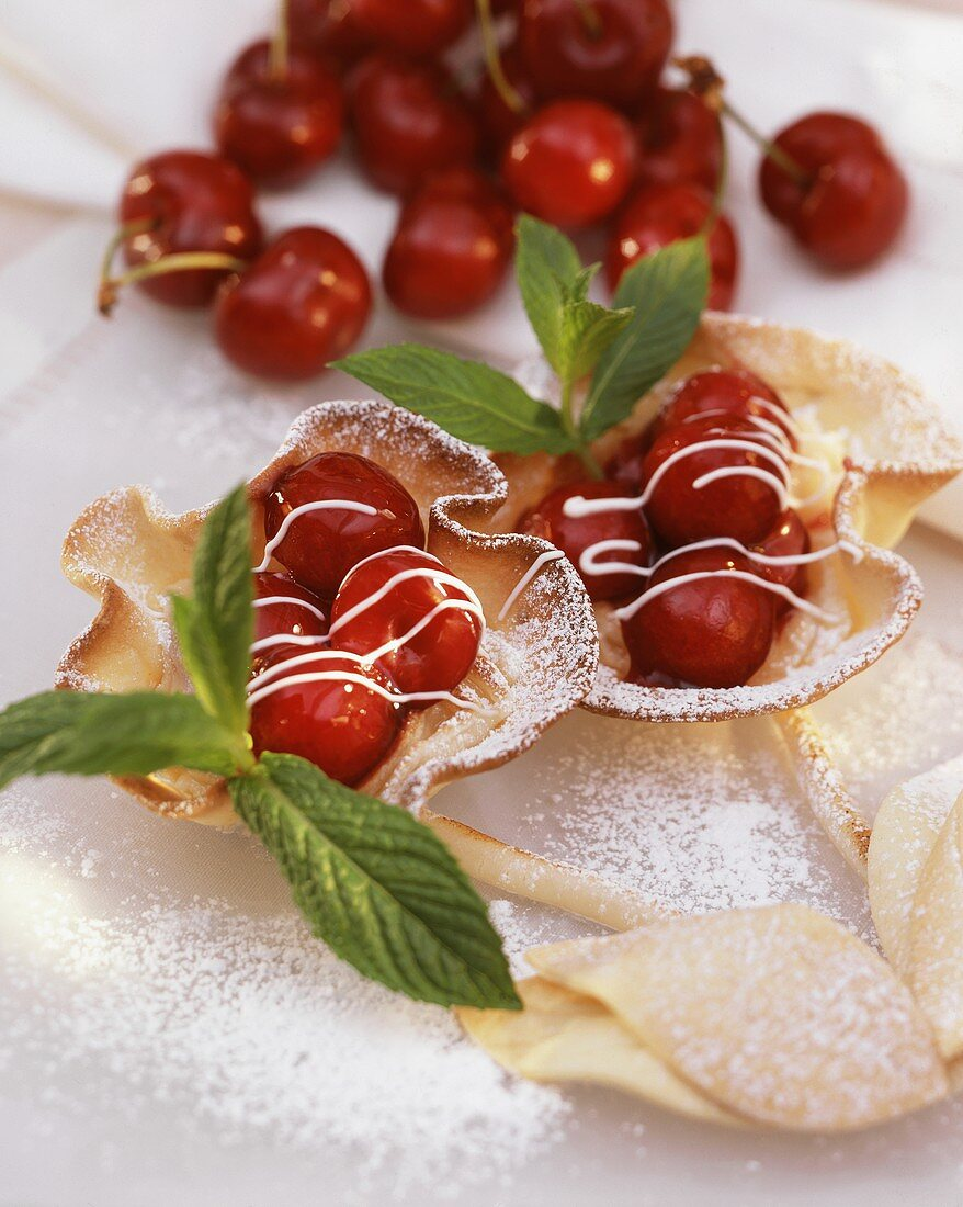 Cherry tartlet with stalk, icing stripes, herb leaf