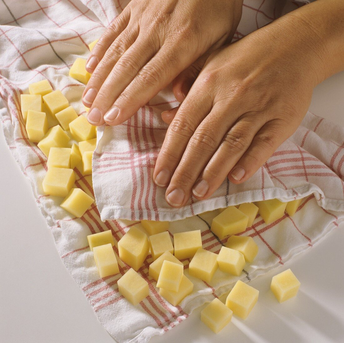 Drying raw potato cubes in kitchen cloth