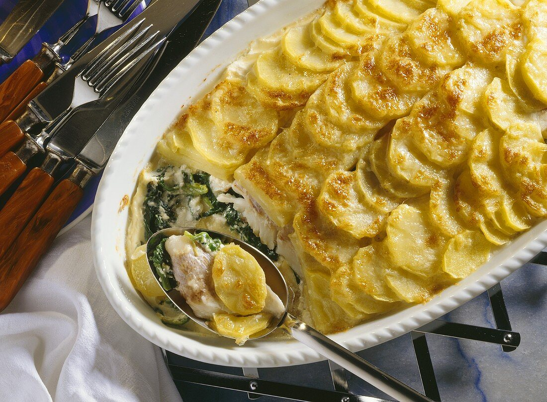 Potato and fish casserole with spinach in baking dish