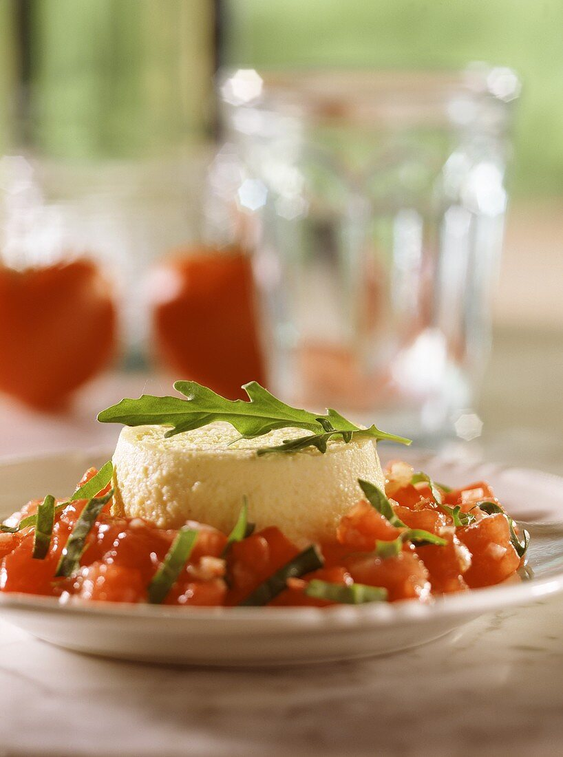 Egg & cheese flan on tomato salad with rocket