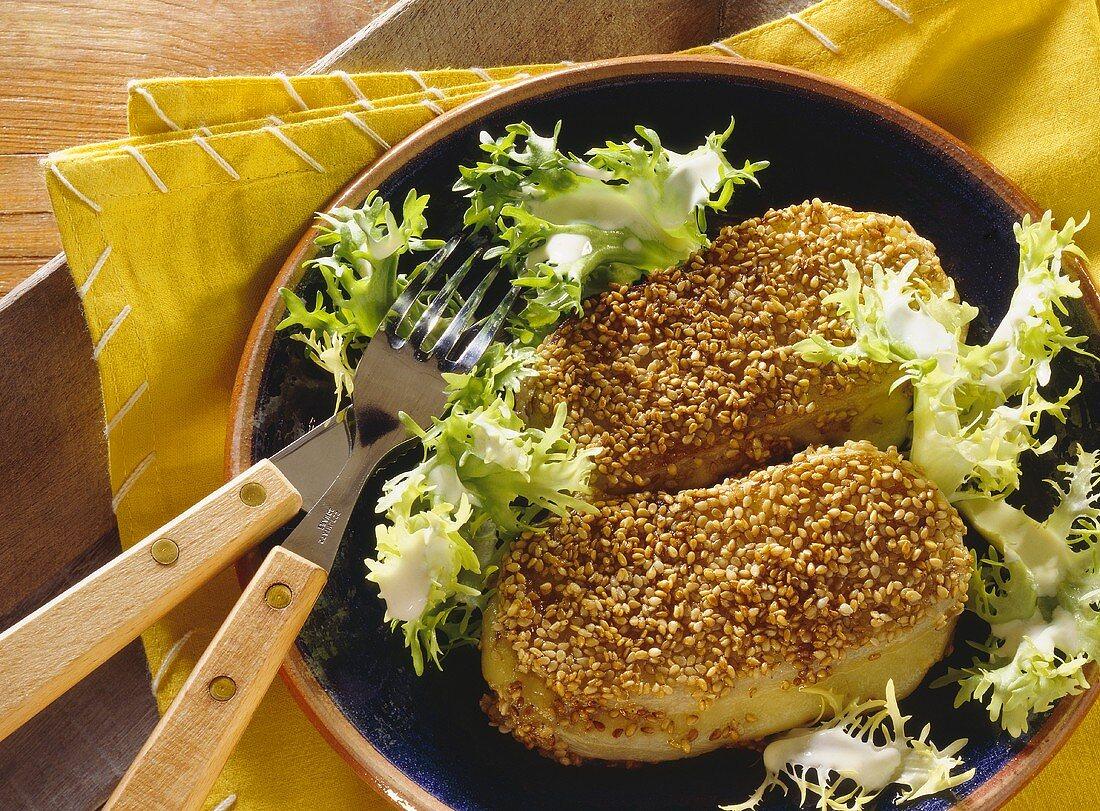 Kohlrabi Cordon bleu with sesame seeds & frisee on plate