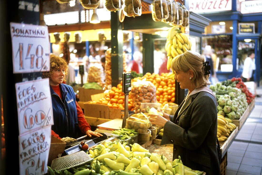Woman buying peppers in market hall, Budapest