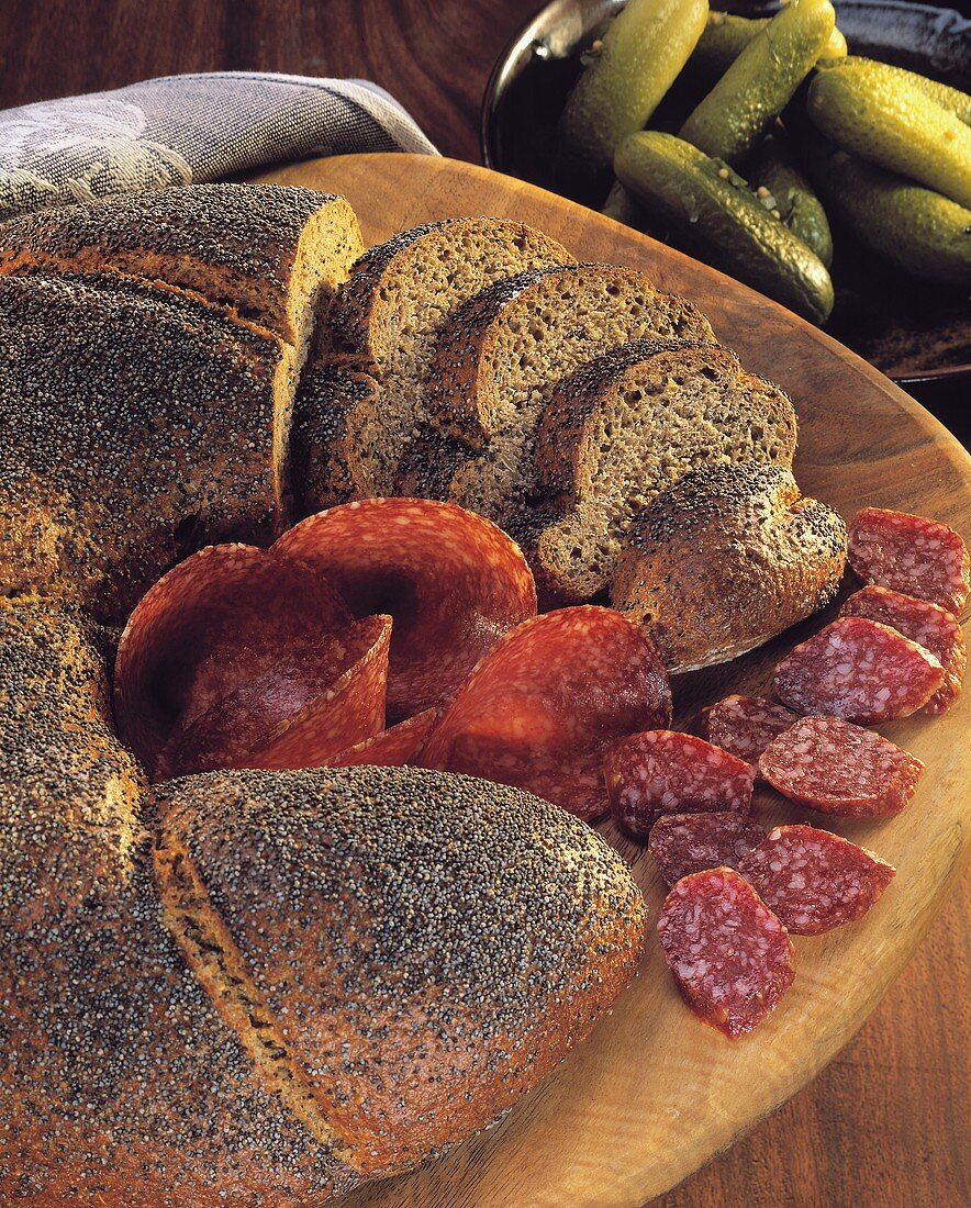 Poppy seed and aniseed bread with salami on a wooden plate