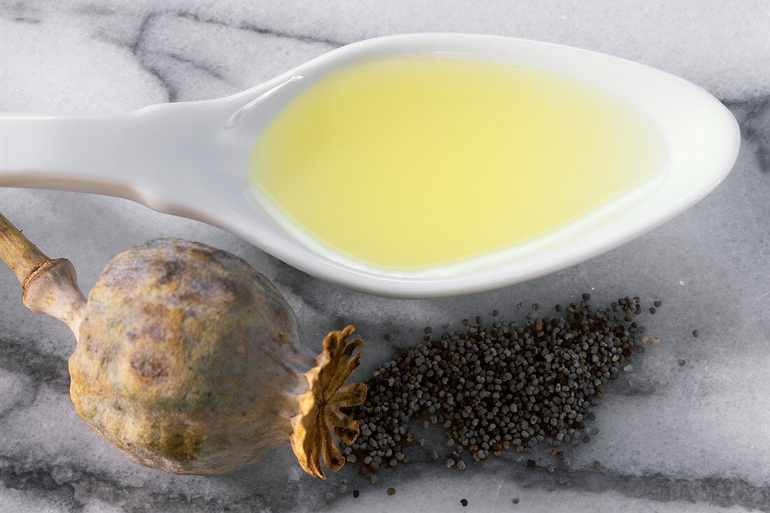 Poppy oil on spoon beside poppy seeds and seed capsules