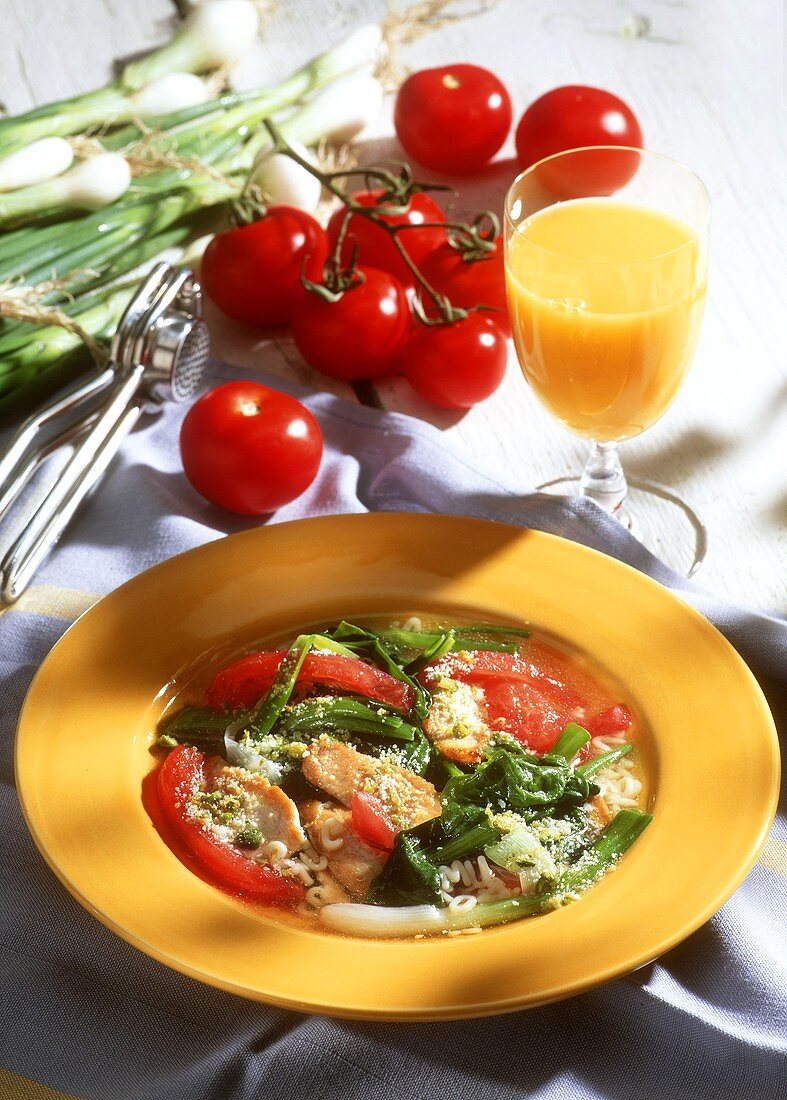 Spinach stew with chicken & tomatoes on plate; orange juice