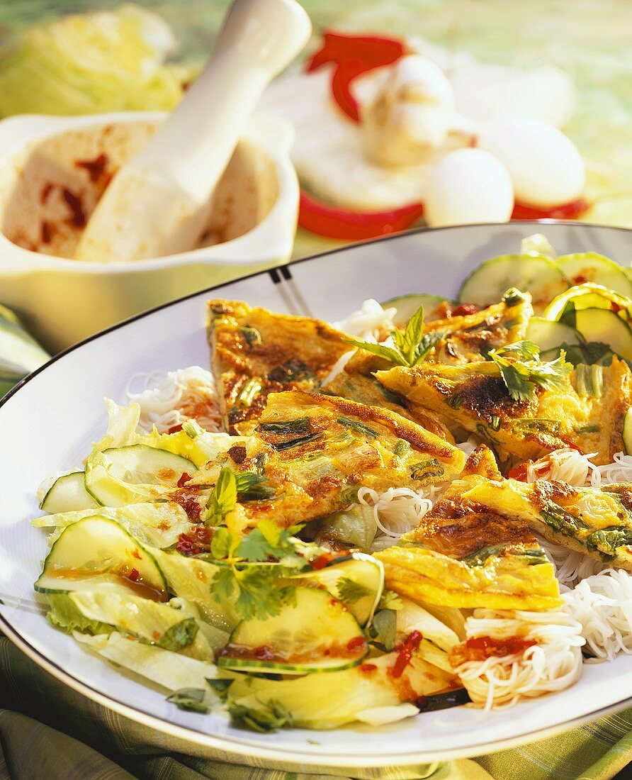Rice noodles with omelette and cucumber salad on plate